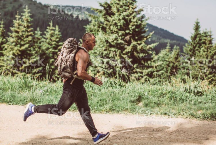 One man, running in nature alone, wearing a backpack.